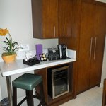 Coffee maker and fridge in room