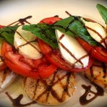 Grilled chicken breasts topped with a fresh caprese salad