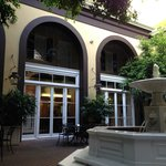 The courtyard is a quiet escape from the bustle of the streets. Lush greens, trickling fountain.
