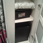 Closet containing fridge, safe, pillow and rail with hangers