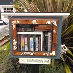 A mini sharing library box outside of a private residence near the inn