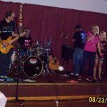 """The """"Cancer Patient"""" singing """"Don't Stop Believing"""" with one of the three bands that donated the"""