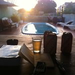 On the table of the bar, facing the pool and drinking beers at sunset!