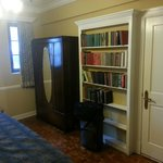 Antique wardrobe and stocked bookshelf stocked with some good books.