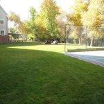 Lawn behind hotel with Tennis and Basketball Court