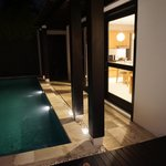 View of private pool and living room at night
