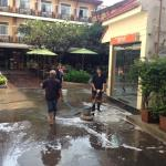 Washing the sidewalk in front of the hotel
