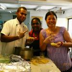 Lisa teaching kitchen staff, Rozie & Tyson, how to make Chines dumplings.