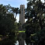 Bok Tower and a beautiful reflecting pond surrounded by massive trees and gardens.