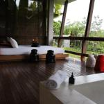 the balcony is equipped with a large bed and a large jacuzzi