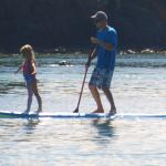 A paddle boarder giving daughter a ride