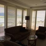 Large seating area surrounded by floor to ceiling windows with plantation style shutters