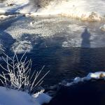 Nearly frozen river in front of cabin.