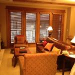living area from the front entry by the kitchen showing balcony, fireplace, and tv above. the co