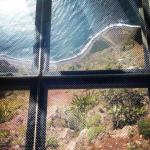 view through the glass floor down onto the mountain side & sea below