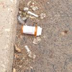The oxycontin pill bottle highlights accumulated curb trash