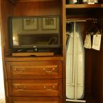 Armoire with TV, dressers, ironing board, coffeemaker, closet