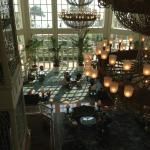 Hotel lobby with grand piano, large ceiling to floor windows and chandeliers