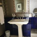 "Pedestal sink in the bathroom. Makeup ""ottoman"" with no real space to use it."