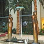 "Masatoyo Kishi ""Sharing"" - 9' tall bronze sculpture of women looking up at a glass camellia"