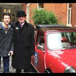 Our doorman and my son standing next to the Mini Cooper.