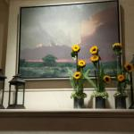 Stormy Texas Hill Country oil painting hanging above hotel lobby's fireplace mantle's rustic lan