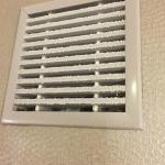 Vent cover on wall in bathroom. DISGUSTING!