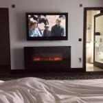 Resting in bed with a view of the television and electric fireplace