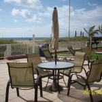 Patio seating by charcoal grills overlooks beach