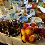 """The """"sweets"""" table of the breakfast room, featuring bread, jams, yogurts, and fruit."""
