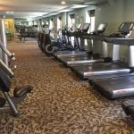 Large gym with several cardio machines, mats some free weights, water and towels