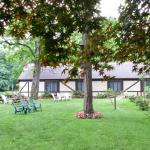 There is a lovely green lawn near a duck pond with picnic tables and seating areas.