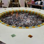 The pretty and warm fire pit in the center of the outdoor patio.