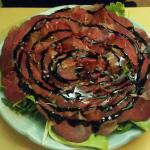 Beef capriccio served over arugula and tomatoes with balsamic dressing.