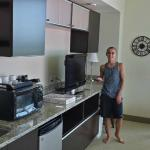 The refrigerator, microwave, counter, TV, desk area, Kuerig brewer, and cupboards/drawers