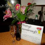 Anniversary card, bubbly & flowers in vase setup for when we arrived