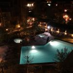 Nighttime view of pool and hot tubs at resort