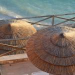 looking down over some chairs & thatched umbrellas