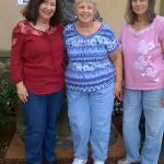 Joy, Gloria, & Linda outside hotel in from of photo sign
