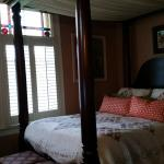 Antique canopy bed with view of stained glass and slatted windows