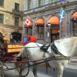 Exterior of L Hotel with horse carriage going by.