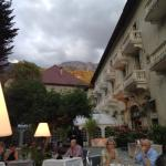Al fresco dining with hotel and Alps in background