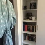 Bath robes on the door, shelves with books and a coffee/tea assortment