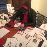 Calligraphy artist in the Museum, writes your name for 20 dirham on a postcard