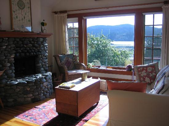 Sooke Harbour House: View frm bed: the lvingroom, stone fireplace and out the picture window