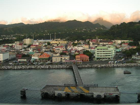 Dominica: Roseau from sea at dusk with clouds over mountains