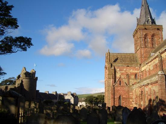 Kirkwall, UK: St Magnus from back of churchyard with Earl's Palace ruins to the left