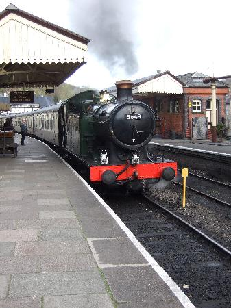 A steam train at the station in Llangollen, grey plume rising from it.