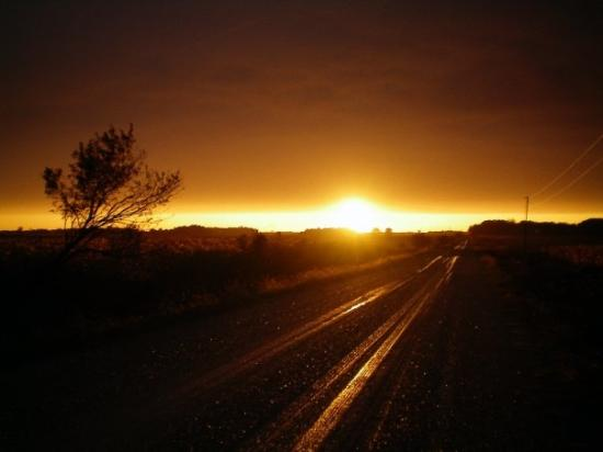 Mason City, : sun set through storm over dirt road (Iowa)
