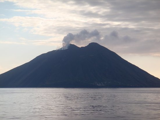 , : Closer look at the smoking volcano, people live at the bottom of it, is amazing.